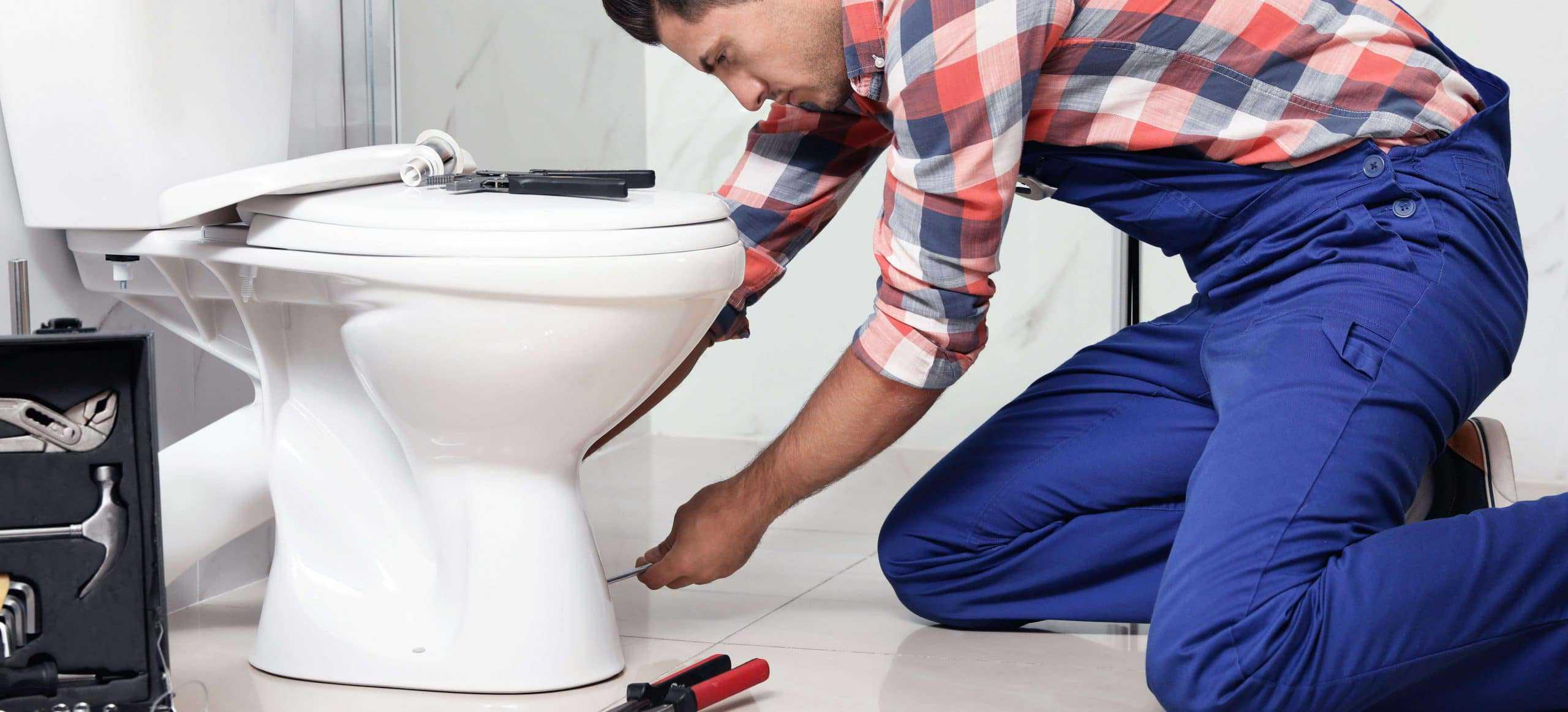 man installing a new toilet